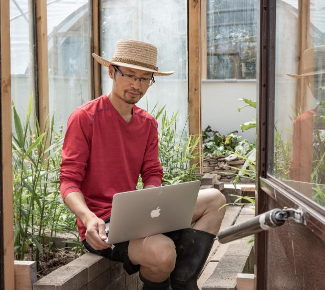 man working on laptop in greenhouse