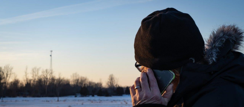 Man on cell phone, winter sunset in background